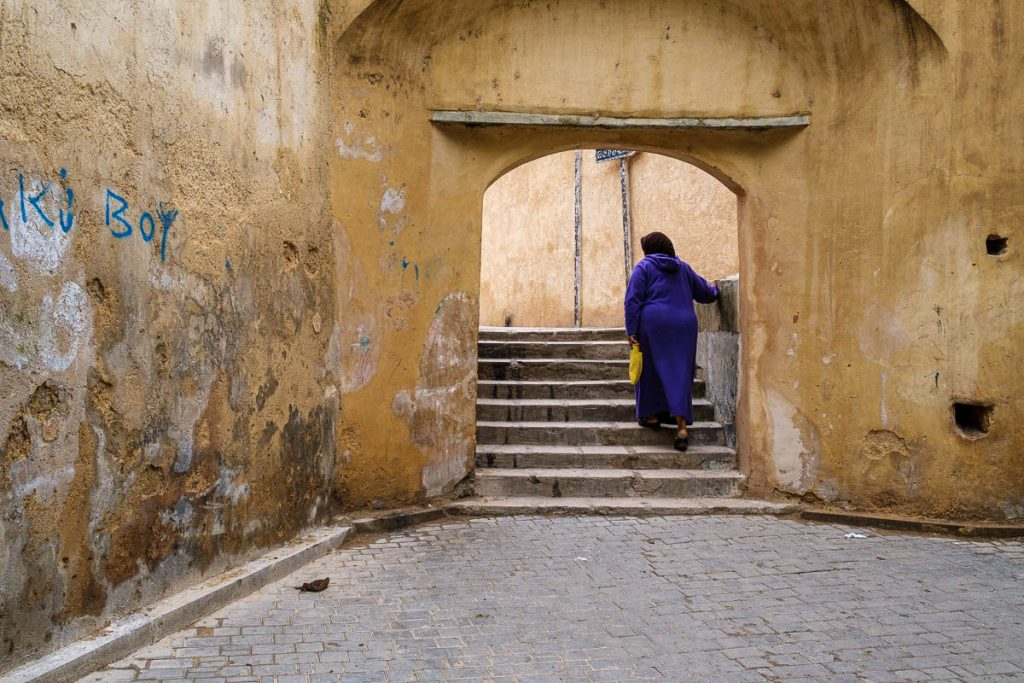 A traditional muslim lady walking through an arch in FES