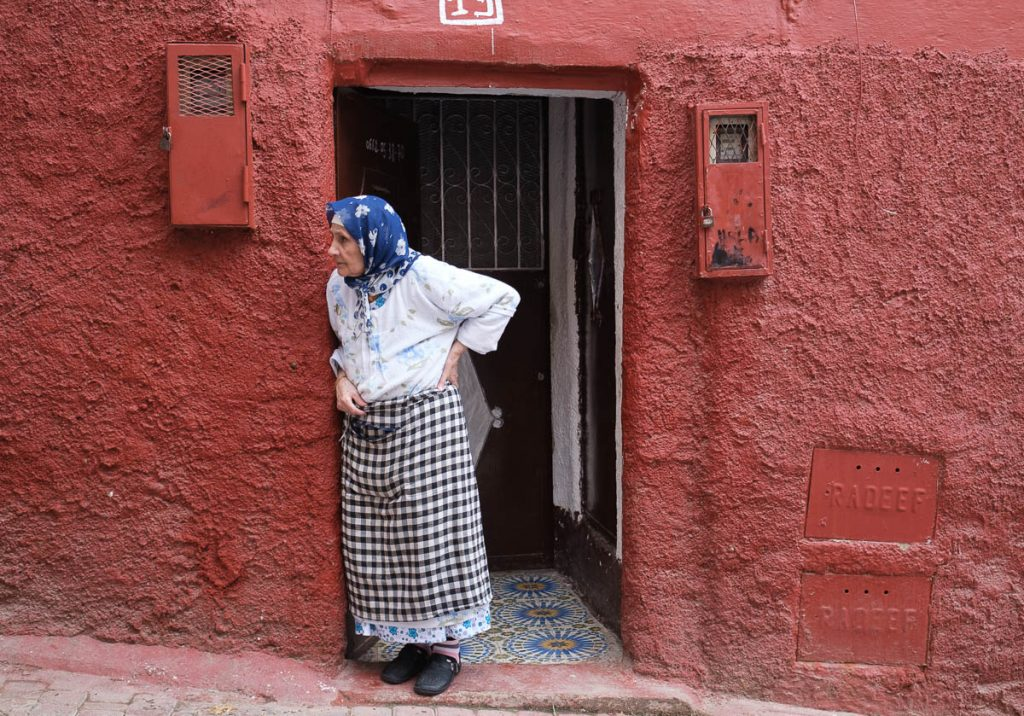 A lady in the jewish quarter of FES standing in the doorway of her house