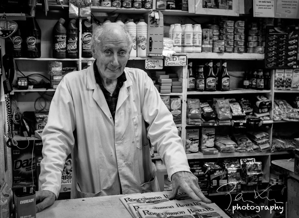 Roscommon shopkeeper with traditional overcoat